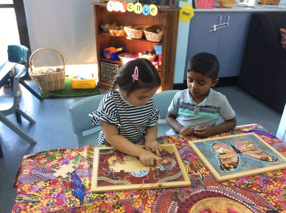 Preschoolers working together to figure out jigsaw puzzle